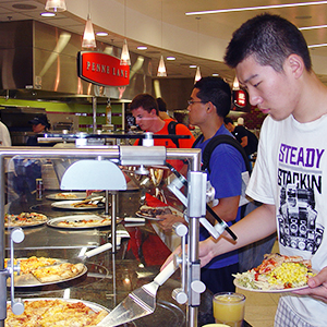 Student selecting pizza at dining hall